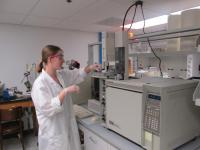 A person wearing a lab coat using a large lab instrument