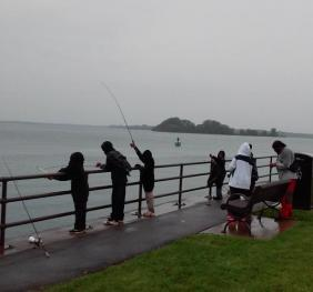 A group of people fishing at the railing at a park near a river