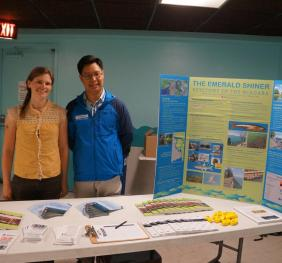 Two people stand behind an informational table with pamphlets and a poster