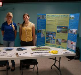 Two people stand behind an informational table with pamphlets and a poster (one is different person than was in Photo 1)