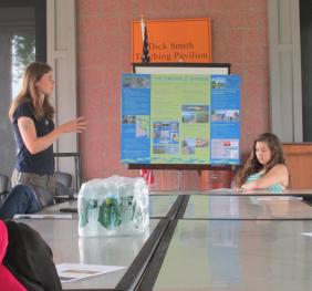 A person presents a poster to a small group of people seated around a table