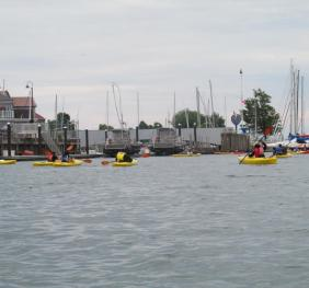 several people in kayaks by a marina