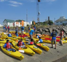 A large group of people sitting in kayaks on a boat ramp