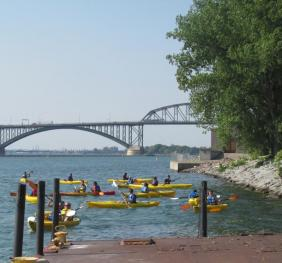 A group of people in kayaks near the shore by a boat dock