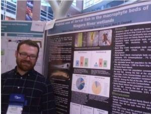 A different person standing in front of a scientific poster