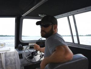 A person inside the cabin of a boat by the helm