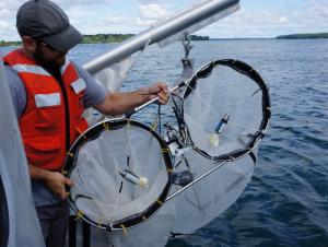 A person on a boat holds up two conical nets that are on a frame side by side