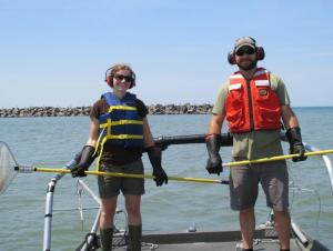 Two people stand at the front of a boat wearing safety gear and holding nets on long poles
