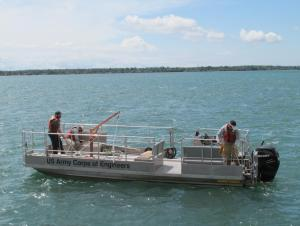 """Three people working on a boat labeled """"US Army Corps of Engineers"""""""