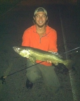 night time picture of a person with a fishing pole holding a large fish